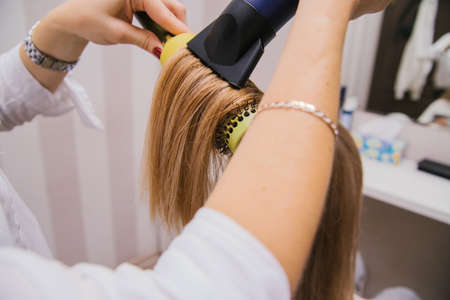 A young woman dries her hair with a hair dryer. The girl combs her hair. Professional hair care products.Beauty salon.
