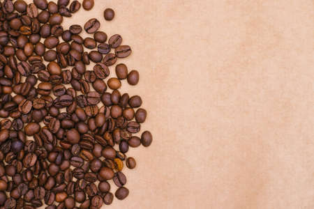Coffee bean background. Dark roasted coffee beans are scattered on the Kraft paper. Texture.