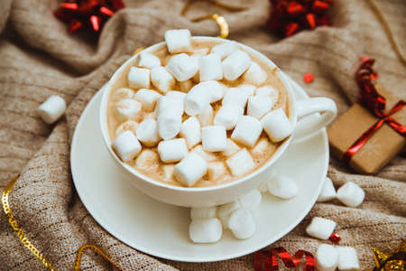 Coffee with marshmallows on a background of knitted fabric with gifts and holiday bows.Hot winter drink. Cocoa and cappuccino.Festive, new year's background. Zdjęcie Seryjne