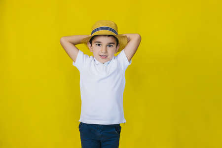 A little boy in a white shirt and straw hat on a yellow background. The gaze is directed at the camera.the concept of recreation and tourism.In the school holidays.