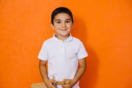 A small boy in a white shirt stands on a yellow background. In the Hands of a child a toy wooden sword. The concept of the game in superhero and defender. In the school holidays. Foto de archivo