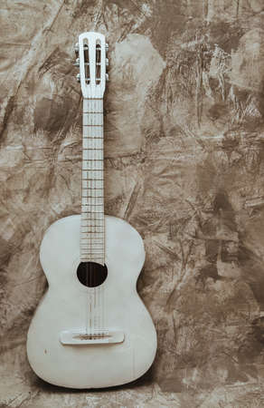A white old guitar stands against a textured gray wall. Guitar as an object in the interior. Decor and decoration. Broken guitar.