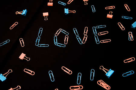 The word love is laid out from paper clips on a black background. The paper clips are pink and blue. The concept of Valentine's Day.