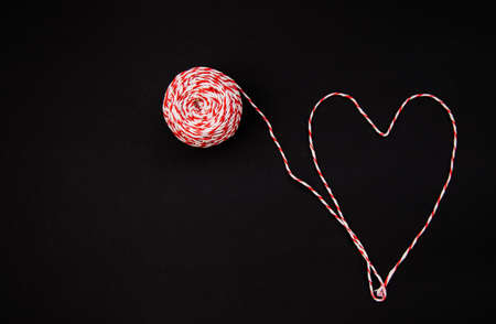 On a black background, a ball of twine is red and white. Threads laid out in the shape of a heart. The concept of Valentine's Day.