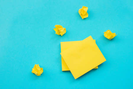 Stickers in the shape of a yellow square are placed on a blue background. Notepads for notes and reminders.Empty space for the text.