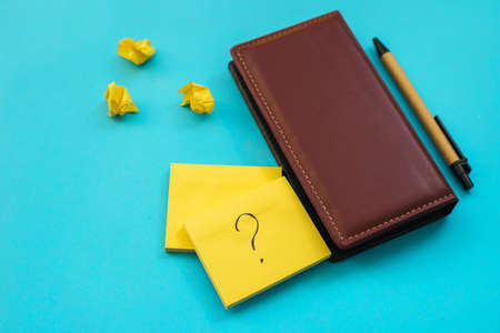 Stickers in the shape of a yellow square are placed on a blue background. Notepads for notes and reminders. A question mark is written on the leaf.