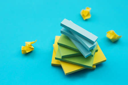 Stickers of different sizes and colors lie on a blue background in the form of a tower. Notepads for notes and reminders.
