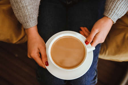 A white cup of coffee in the girl's hands. A cup and saucer are in the lap of a young woman. The woman is dressed in blue jeans and a sweater. Cozy and atmospheric photo. Winter warm drink.