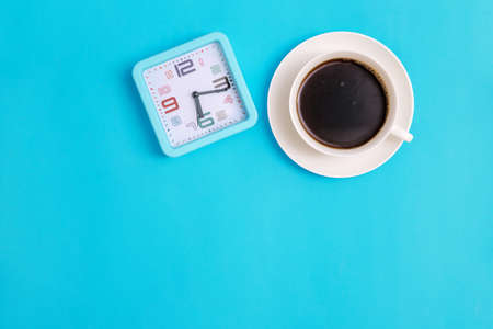 White cup with black coffee clock on blue background. Morning breakfast. Time for rest and work. Empty space for the text. Minimalistic photography.