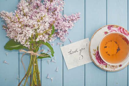 Tarjeta de gracias, ramo verano de hermoso color lila que florece y el té negro Inglés en china taza de té con el platillo Foto de archivo - 44437088