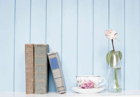 ancient books: Old antiquarian ancient books, china cup and rose in the bottle on bookshelf on the blue wooden background Stock Photo
