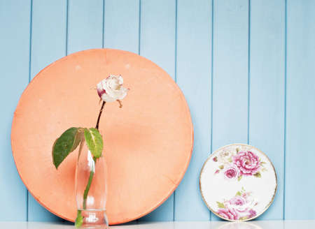 tea cosy: China tea saucer with victorian rose, white rose in the bottle on the shelf on blue wooden background Stock Photo
