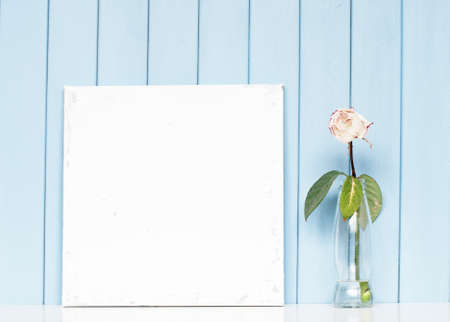 Un lienzo en blanco mezquino y rosa blanca en la botella en el fondo de madera azul Foto de archivo - 44713543