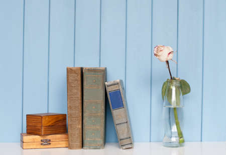 antiquarian: Ancient antiquarian books are stacked on home bookshelf with rose in the bottle of water and two vintage wooden boxes on blue wooden background