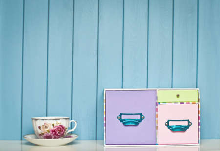 pedant: old vintage multicolored box and victorian english china cup on the shelf on blue wooden background