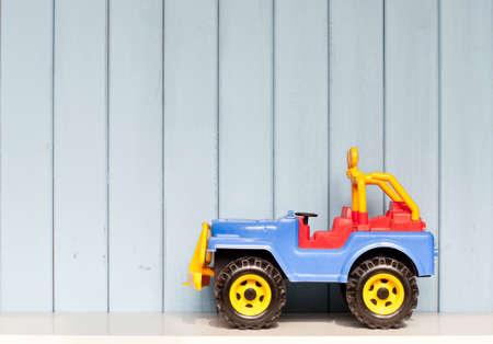 plastic speelgoed auto jeep op de boekenplank in de kamer van de kinderen op blauwe houten achtergrond