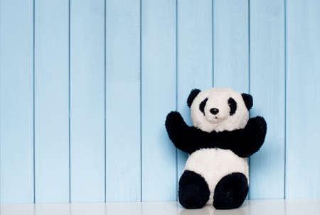 oso panda: viejo panda de la vendimia juguete suave en la estantería en la habitación de los niños en el fondo de madera azul Foto de archivo