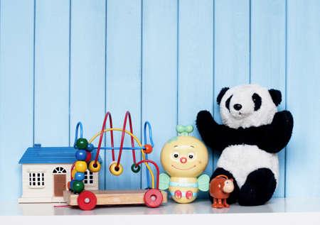juguetes: Casa del juguete, panda de época antigua, abeja mecánica, mono de relojería y el laberinto en espiral en la estantería en la habitación de los niños en el fondo de madera azul