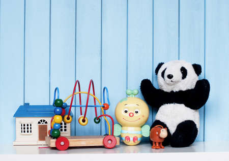 Toy house, old vintage panda, mechanical bee, clockwork monkey and spiral labyrinth on the bookshelf in the childrens room on blue wooden background Stock Photo
