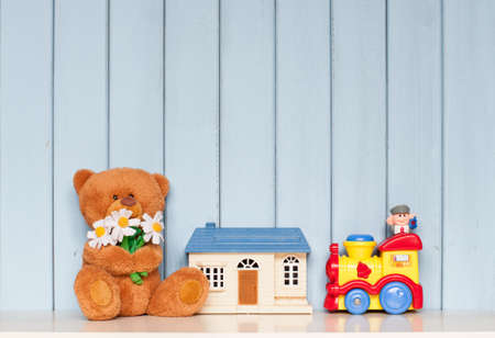 kids toys: soft teddy bear with flowers, toy house and mechanical locomotive on the bookshelf on blue wooden background in the childrens room