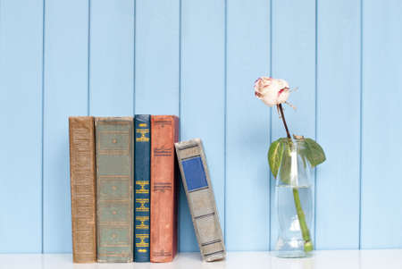 antiquarian: Ancient antiquarian books are stacked on home bookshelf with rose in the bottle of water on blue wooden background