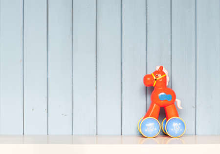 plastic toy horse on the bookshelf in childrens room on blue wooden background Stock Photo