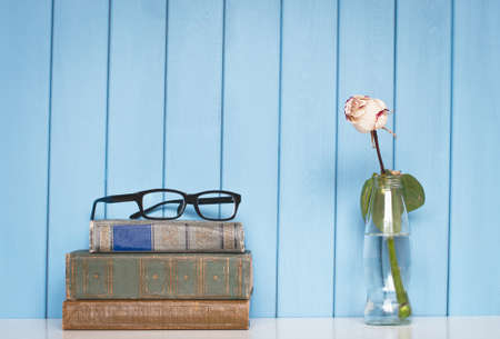 antiquarian: Ancient antiquarian books are stacked on home bookshelf with rose in the bottle of water and glasses on blue wooden background