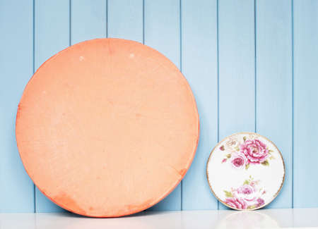 tea cosy: China tea saucer with victorian rose on the shelf on blue wooden background Stock Photo