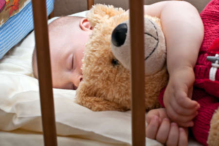 regimen: little baby is sleeping in his bed with his toy Stock Photo