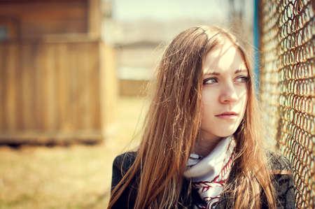 Девушка, глядя через забор на осенней пляже Фото со стока