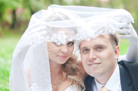 Happy young husband and wife are looking at camera