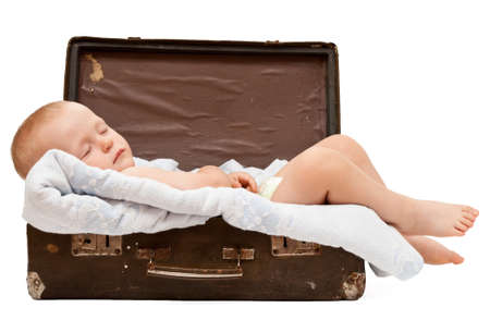 baby sleeps in the old shabby suitcase