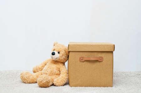 Osito de peluche y caja textil marrón con asas y tapa en el fondo blanco Foto de archivo - 45391341