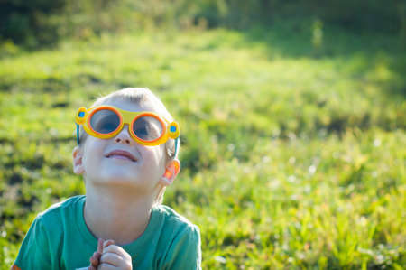 imaginarium: Boy in 3d glasses sitting on green grass in the park