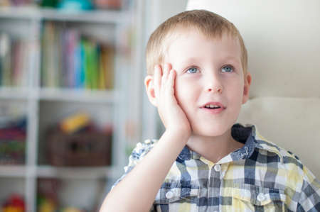 tells: Little cheerful child is dreaming in childrens room Stock Photo