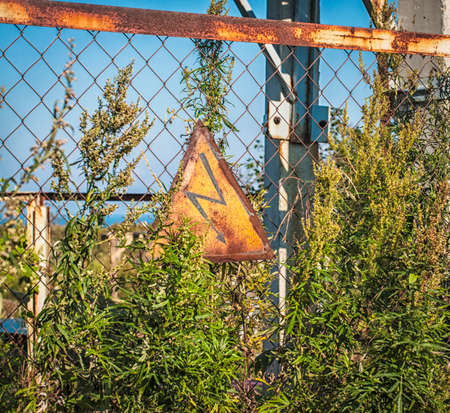 amperage: high voltage grunge sign on rusty fence Stock Photo