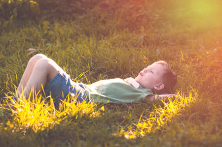 peacefully: Child peacefully sleeps after lunch on green grass in sunny countryside
