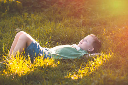 Child lies on green grass in sunny countryside, le petit prince Stock Photo