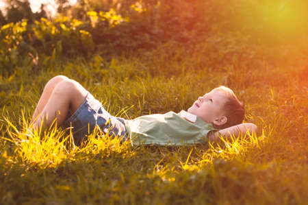 prince of peace: Child lies on green grass in sunny countryside, le petit prince Stock Photo