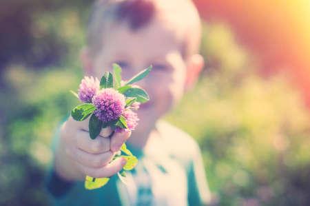 息子は、ママを与える紫色のクローバーの束 写真素材