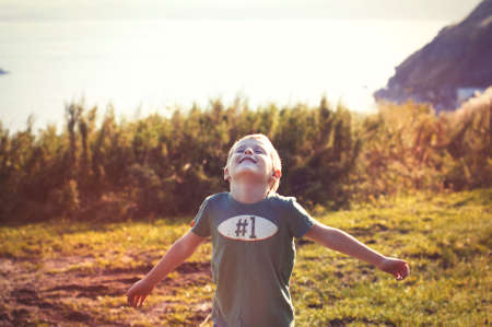 wonderful: Happy cheerful smiling little child walking in the autumn park on a sunny day and enjoying wonderful successful life and warm weather Stock Photo
