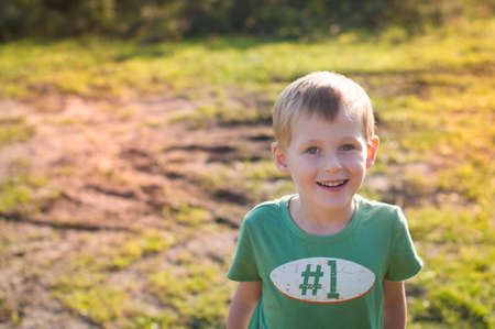 misbehave: happy cheerful boy walking outdoors in sunny morning autumn forest Stock Photo