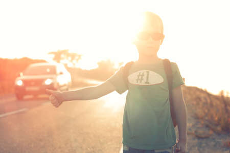 hitchhiking: Little child hitchhiking alone summer sunset background Stock Photo