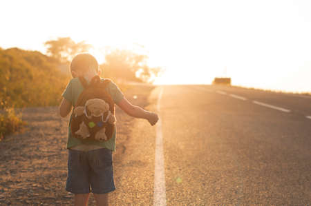Lost child standing on the road hitchhiking on a sunset Stock Photo