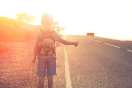 lost: Lost child standing on the road hitchhiking on a sunset Stock Photo