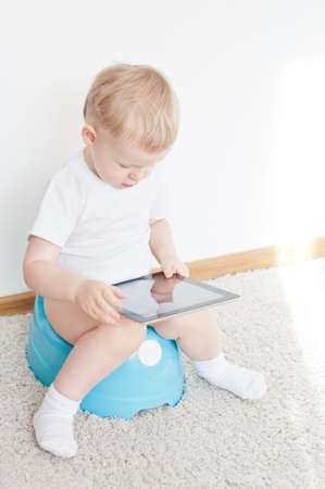 little boy on potty with tablet pc on the  white carpet Reklamní fotografie