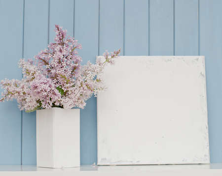 Gentle bunch of lilac in white vase and blank canvas on the table on blue wooden background