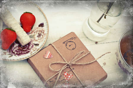 valentine          s day candy: Spring still life with parcel, tea, marzipan and white chocolate sweets and dry bouquet