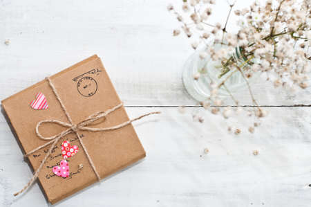 Gift package wrapped with paper, rope with hearts and dry bouquet on vintage wooden background