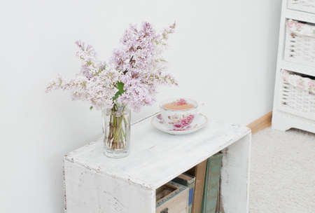 curio: lilac bouquet and tea in china teacup on the vintage nightstand